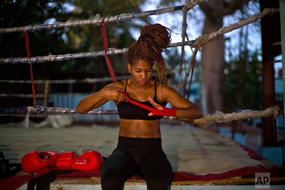 In this Jan. 24, 2017 photo, boxer Idamelys Moreno wraps a bandage on her hand before a training session at a sports center in Havana, Cuba. Boxing has long been an athletic engine for Cuba, which has won 72 Olympic medals in that category but women are not allowed to box. (AP Photo/Ramon Espinosa)