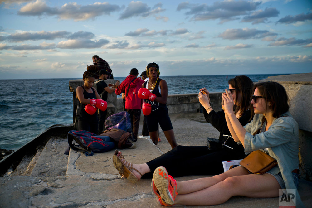 In this Jan. 30, 2017 photo, boxers Idamelys Moreno, left, and Legnis Cala, get ready for a photo session, as tourists take photos of the sunset, on Havana's sea wall in Cuba. Female athletes in Cuba have made strides in many other sports, including wrestling, judo and most recently, weightlifting, but not in boxing. (AP Photo/Ramon Espinosa)