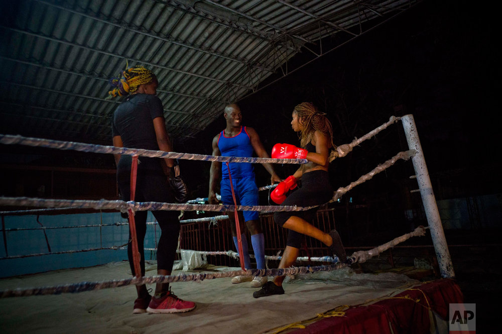 In this Jan. 24, 2017 photo, Olympic silver medalist Emilio Correa Jr., center, instructs Idamelys Moreno, right, and Legnis Cala, at a sports center in Havana, Cuba. Once when the women were kicked out a of boxing gym, Correa Jr. stepped in to help some of them find another gym while they push top Cuban officials to support female boxing. (AP Photo/Ramon Espinosa)