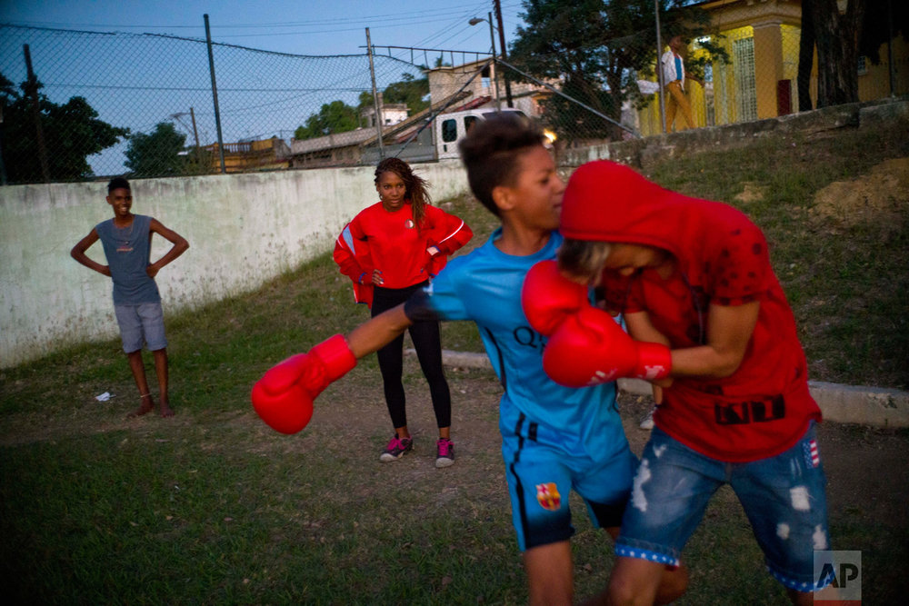 In this Jan. 19, 2017 photo, boxer Idamelys Moreno, center back, looks at children playing around, at a sports center in Havana, Cuba. Boxing has long been an athletic engine for Cuba, which has won 72 Olympic medals in that category but women are not allowed to box. (AP Photo/Ramon Espinosa)