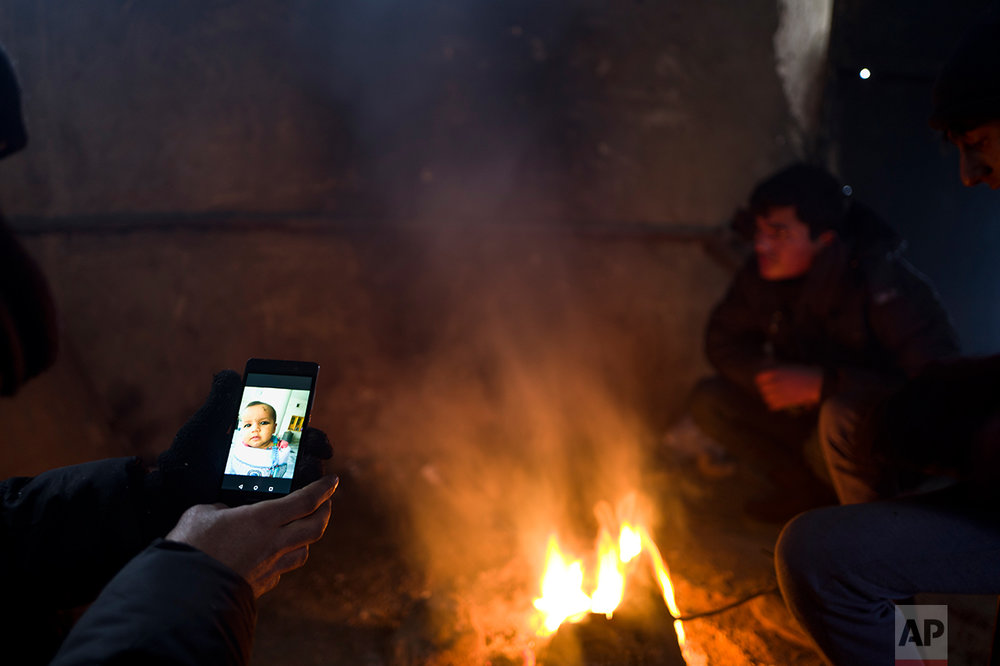 Refugee Ayoub Ahmadzai, 35, from Kandahar, Afghanistan looks at a picture of his daughter Tamana on his mobile phone, while he and others took refuge in an abandoned warehouse in Belgrade, Serbia, Saturday, Jan. 28, 2017.  (AP Photo/Muhammed Muheisen)