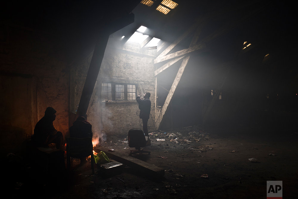 An Afghan refugee man, center, shaves his beard while others warm themselves around a fire, in an abandoned warehouse in Belgrade, Serbia, Sunday, Jan. 29, 2017. (AP Photo/Muhammed Muheisen)