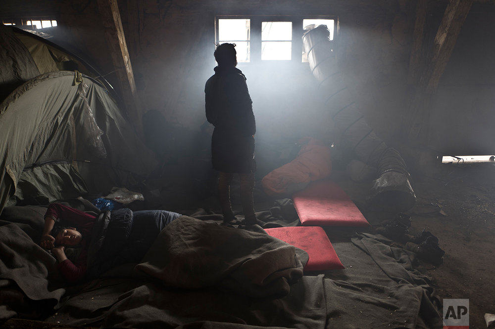 An Afghan refugee man sleeps on the ground while another looks out a window in an abandoned warehouse where they and other migrants took refuge in Belgrade, Serbia, Wednesday, Feb. 1, 2017. (AP Photo/Muhammed Muheisen)