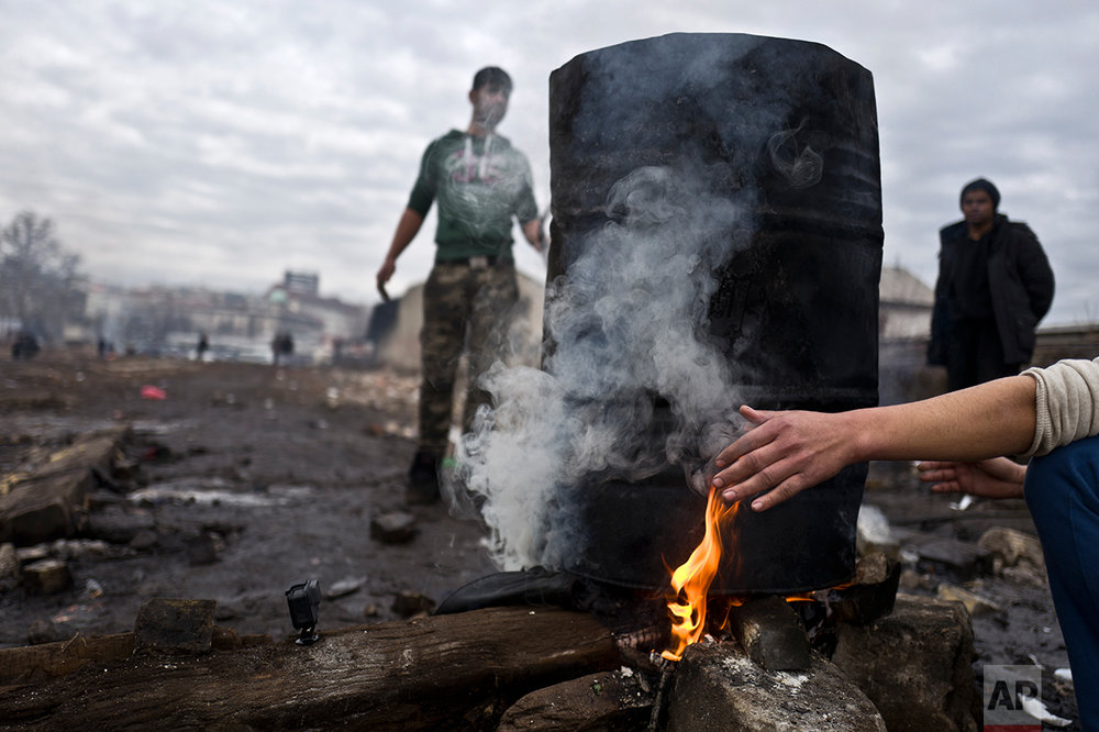 An Afghan refugee youth warms his hand while waiting for the water to boil and have a shower outside an abandoned warehouse where he and other migrants are taking refuge in Belgrade, Serbia, Thursday, Feb. 2, 2017. (AP Photo/Muhammed Muheisen)