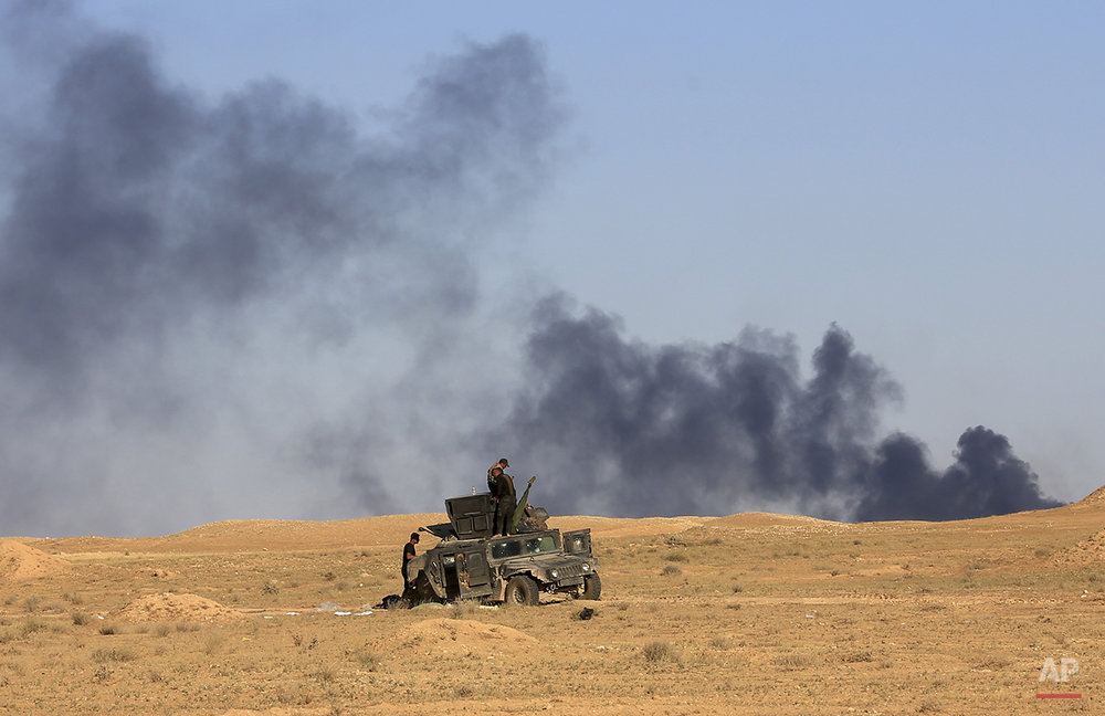 Iraq's elite counter terrorism forces advance in Hit, 85 miles (140 kilometers) west of Baghdad, Iraq, Monday, April 4, 2016. Iraqi forces say they have entered the western Islamic State group-held town of Hit Monday after an operation to retake it was relaunched last week. (AP Photo/Khalid Mohammed)