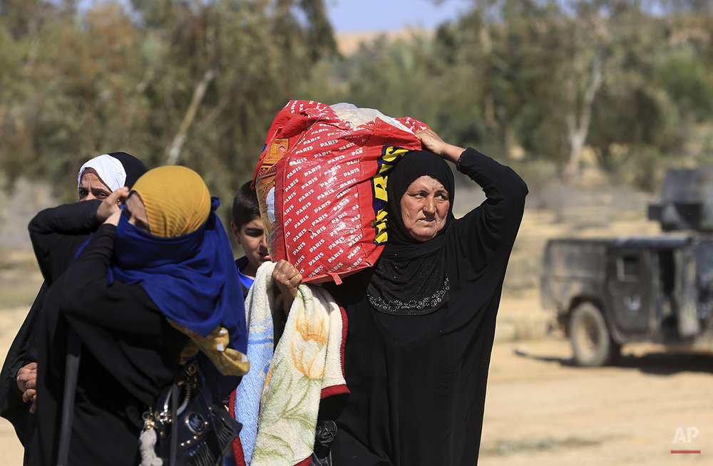 Iraqi women flee their homes during clashes between Iraqi security forces and Islamic State group in Hit, 85 miles (140 kilometers) west of Baghdad, Iraq, Monday, April 4, 2016. Families, many with small children and elderly relatives say they walked for hours Monday through desert littered with roadside bombs to escape airstrikes and clashes. (AP Photo/Khalid Mohammed)