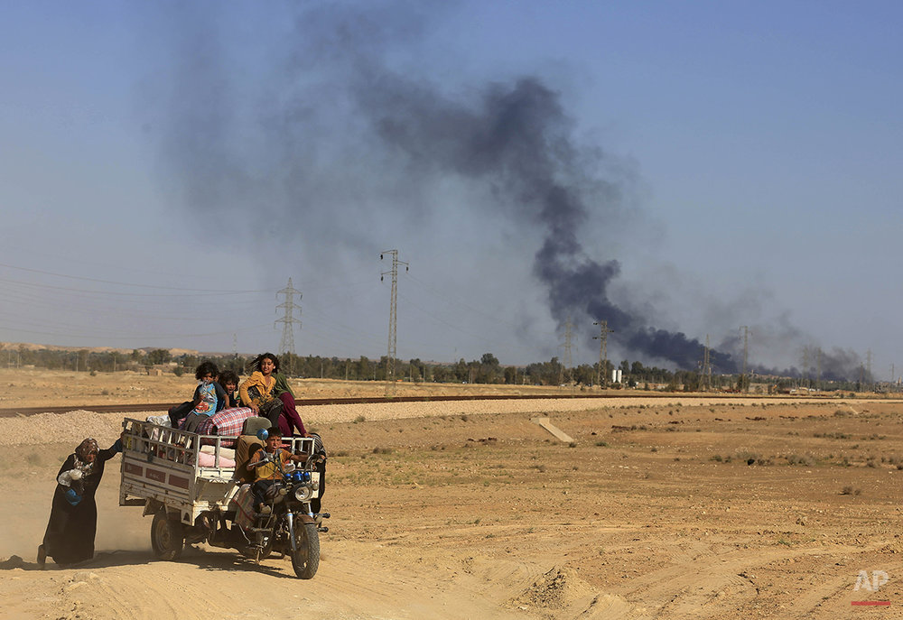 Smoke rises as people flee their homes during clashes between Iraqi security forces and Islamic State group in Hit, 85 miles (140 kilometers) west of Baghdad, Iraq, Monday, April 4, 2016. Families, many with small children and elderly relatives say they walked for hours Monday through desert littered with roadside bombs to escape airstrikes and clashes. (AP Photo/Khalid Mohammed)