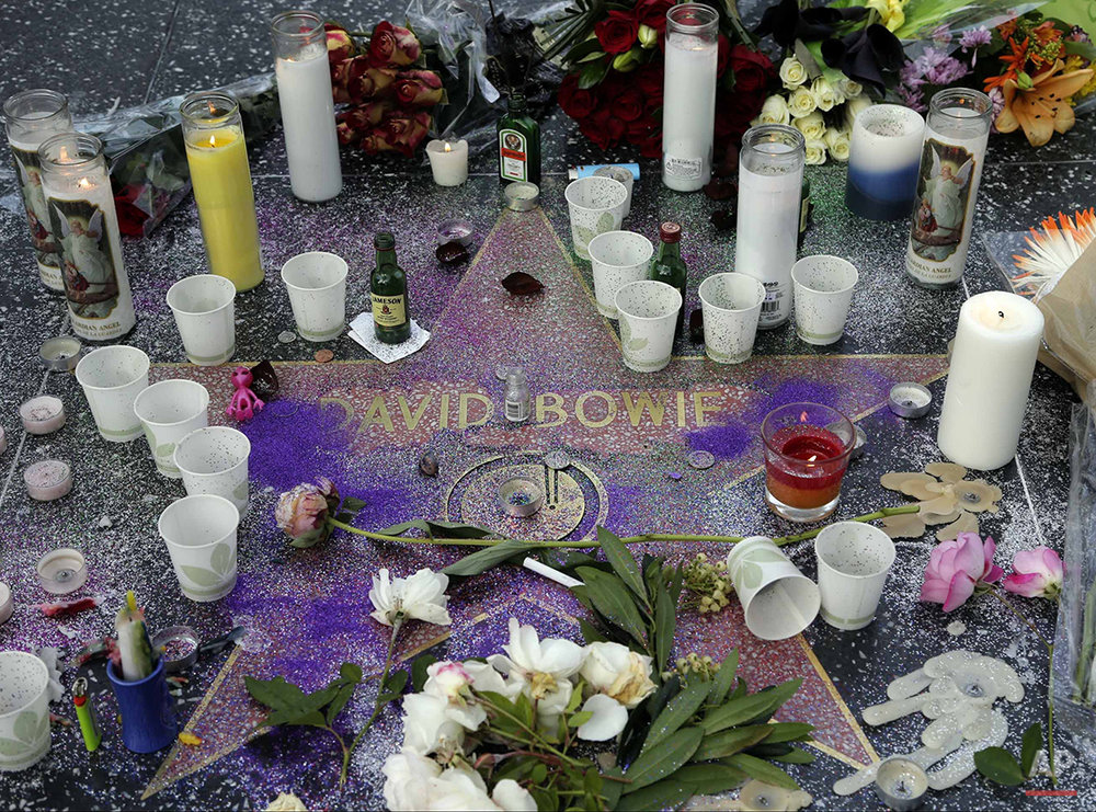 A makeshift memorial surrounds David Bowie's star on the Hollywood Walk of Fame in Los Angeles, Monday, Jan. 11, 2016. Bowie, the other-worldly musician who broke pop and rock boundaries with his creative musicianship, nonconformity, striking visuals and a genre-spanning persona he christened Ziggy Stardust, died of cancer Sunday. He was 69 and had just released a new album. (AP Photo/Nick Ut)