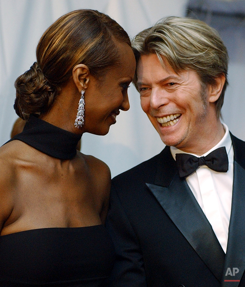 In this June 3, 2002, photo, Iman, left, and her husband, singer David Bowie arrive at the Council of Fashion Designers of America Fashion Awards in New York. (AP Photo/Suzanne Plunkett)