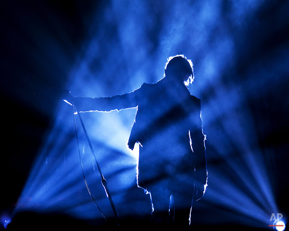 Rock icon David Bowie is backlit as he rises from beneath the stage for the start of his concert at the Fleet Center in Boston, Tuesday, March 30, 2004. (AP Photo/Robert E. Klein)