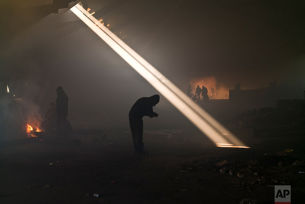 A group of migrants, left, gather around a fire to warm themselves in an abandoned warehouse in Belgrade, Serbia, Monday, Jan. 30, 2017. (AP Photo/Muhammed Muheisen)