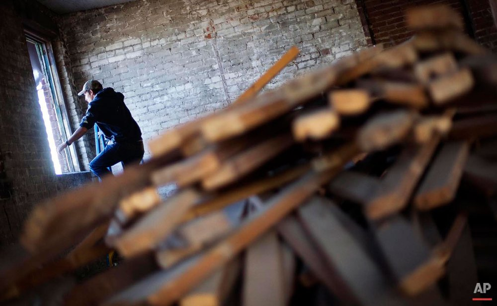 Reclaimed wood sits in the foreground as Glen Wilson, 22, crawls onto the roof of the Coalfield Development Corp. for a class on installing solar panels Monday, Oct. 5, 2015, in Huntington, W.Va. The program hires graduates of high school vocational programs to restore, repurpose or tear down old buildings, use old building materials to make furniture, or build new homes on reclaimed coalfield land. Employees also are also required to take six hours of community college courses a week and three hours of life skills classes that help them with things like money management and healthy eating. (AP Photo/David Goldman)