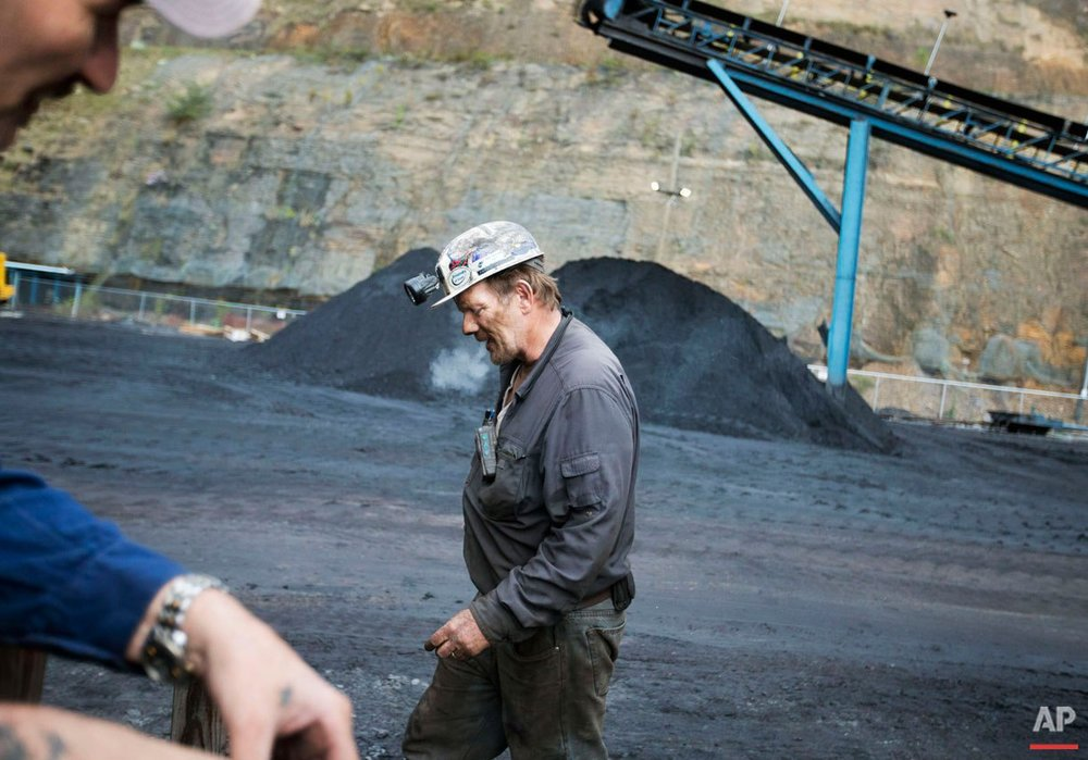 "Foreman John Dillon, a coal miner of 39 years, walks past piles of coal at the Sewell ""R"" coal mine Tuesday, Oct. 6, 2015, in Yukon, W.Va. In the U.S., where natural gas has become a cheaper alternative to coal to generate electricity, miners are facing an especially difficult market: Four major U.S. coal companies have filed for bankruptcy protection in the last 18 months. (AP Photo/David Goldman)"
