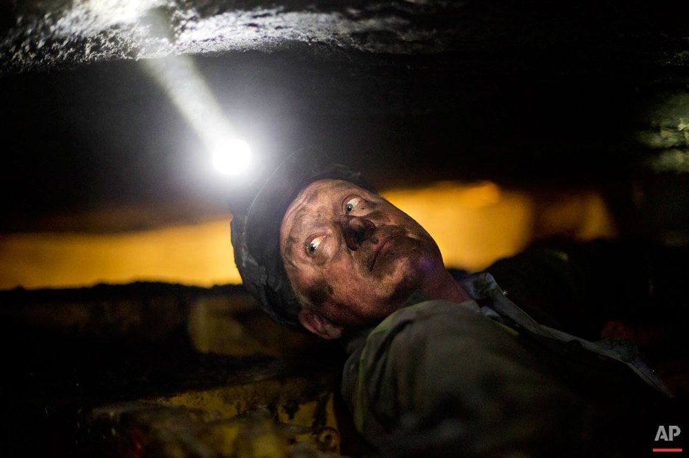 Scott Tiller, a coal miner of 31 years, takes a break while operating a continuous miner machine in a coal mine roughly 40-inches-high, Tuesday, Oct. 6, 2015, in Welch, W.Va. The seams of coal in the mine are so thin workers can barely squeeze down them. They enter on carts nearly flat on their backs, the roof of the mine coursing by just a few inches in front of their faces. They don't stand up all day. (AP Photo/David Goldman)