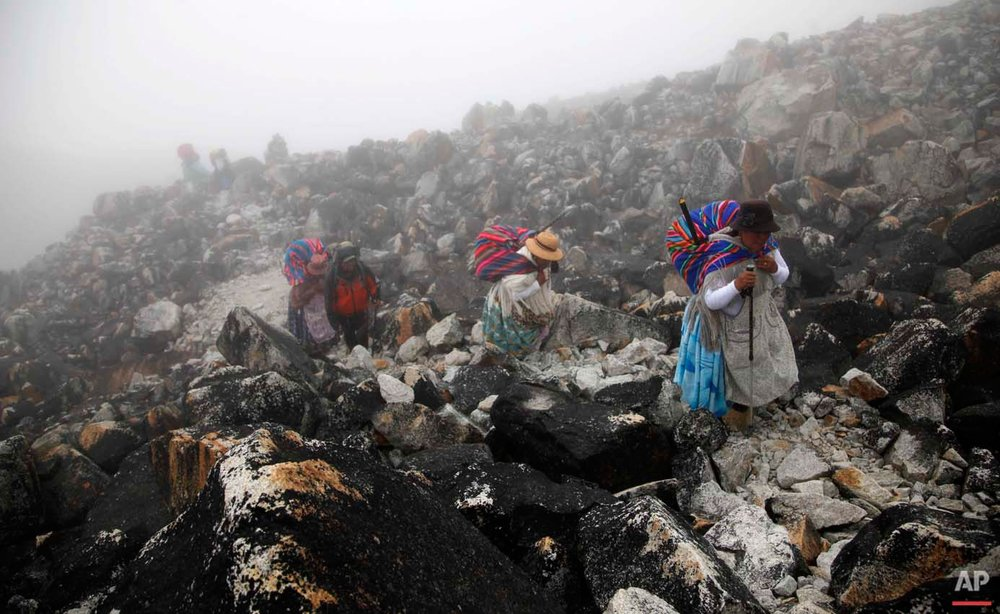 "In this Dec. 16, 2015 photo, Aymara indigenous women walk through the fog with their guide, up the Huayna Potosi mountain on the outskirts of El Alto, Bolivia. As they climb, the women wear thermal sweat suits under their traditional ""cholita"" clothing. Only in the last part of the climb up to the top do the women remove their skirts, to prevent accidents. (AP Photo/Juan Karita)"