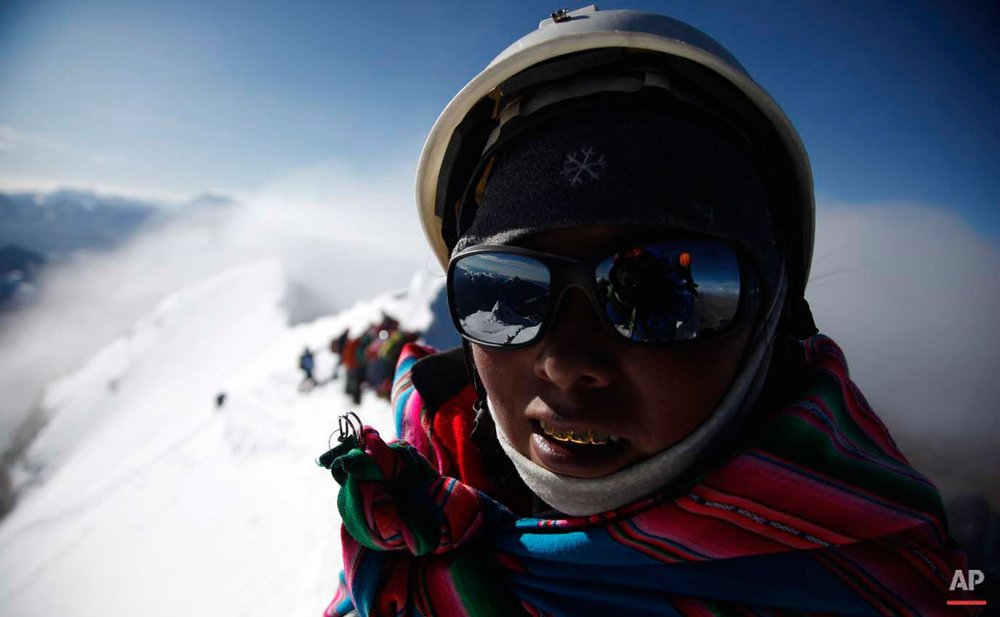 In this Dec. 17, 2015 photo, the sunglasses of Aymara indigenous woman Janet Mamani Callisaya reflect the Huayna Potosi mountain as she pauses during her hike up the snowy peak on the outskirts of El Alto, Bolivia. At first glance, indigenous Bolivian women don't look much like mountain climbers, with their colorful, multilayered skirts and fringed shawls. But their helmets, polarized goggles and crampons attached to their shoes for climbing give them away. (AP Photo/Juan Karita)