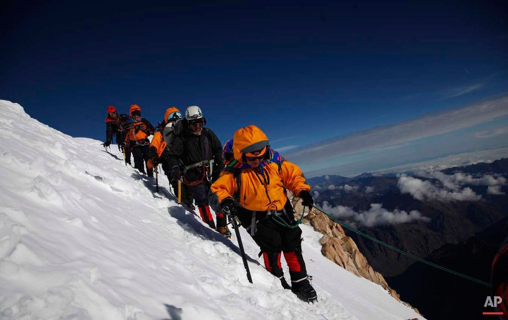 In this Dec. 17, 2015 photo, Aymara indigenous women walk with their guide as they descend the snow capped Huayna Potosi mountain on the outskirts of El Alto, Bolivia. Eleven Aymara women, ranging in age from 20 to 50 years old, made the two-day climb up the mountain. All of the women work as porters and cooks at the base camp, but six of the youngest ones would like to eventually join the ranks of the men and guide tourists to the peak. (AP Photo/Juan Karita)