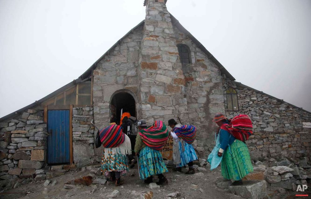 "In this Dec. 16, 2015 photo, Aymara indigenous women enter the Campo de Roca shelter for hikers as they climb the Huayna Potosi mountain on the outskirts of El Alto, Bolivia. Domitila Alana Llusco said she had a hard time finding appropriate gear she could afford when she started 15 years ago. ""My feet are small, there are no boots,"" she said. ""But nothing stopped me and I have reached the peak of three mountains."" (AP Photo/Juan Karita)"
