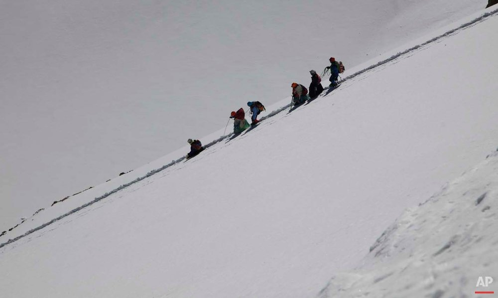 In this Dec. 17, 2015 photo, Aymara indigenous women walk with their guide down the snow capped Huayna Potosi mountain on the outskirts of El Alto, Bolivia. Eleven Aymara women, ranging in age from 20 to 50 years old, made the two-day climb up the mountain. All of the women work as porters and cooks at the base camp, but six of the youngest ones would like to eventually join the ranks of the men and guide tourists to the peak. (AP Photo/Juan Karita)