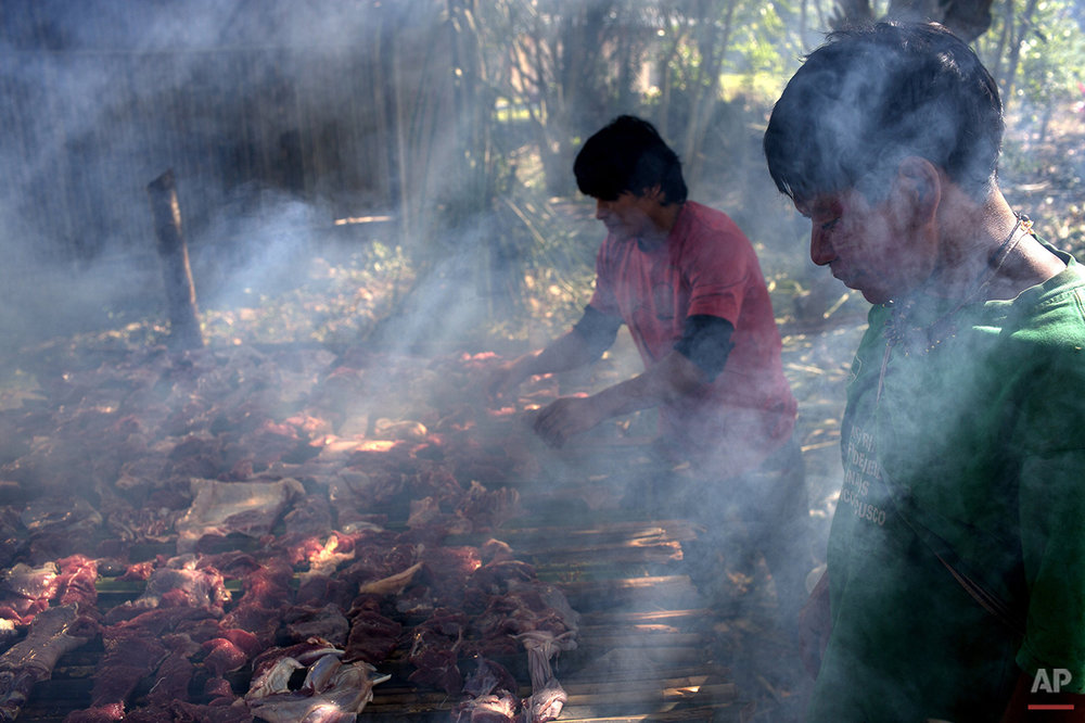 In this June 22, 2015 photo, Ashaninka Indian men smoke meat on a grill made from bamboo canes, in the Otari Nativo village, Pichari, Peru. The strips of meat come from a cow that was donated by municipal authorities to mark the 44th anniversary of their community's founding. (AP Photo/Rodrigo Abd)