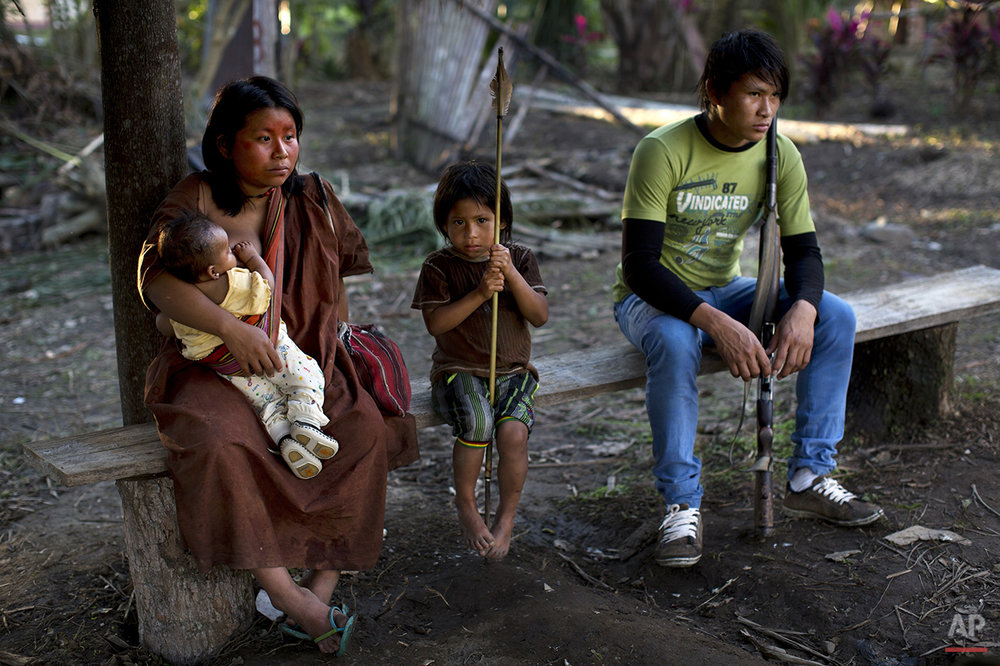 In this June 23, 2015 photo, a couple gather with their sons in Otari Nativo village, Pichari, Peru. The man holds a rifle. (AP Photo/Rodrigo Abd)
