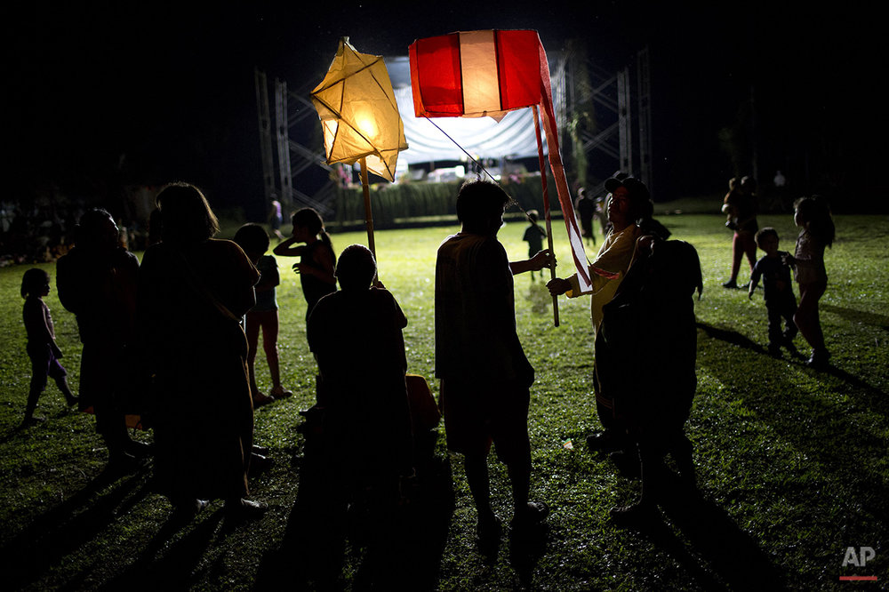 In this June 23, 2015 photo, Ashaninka Indian school children parade with lanterns during celebrations marking the 44th anniversary of the founding of their village, Otari Nativo, Pichari, Peru. The Ashaninka people number in the tens of thousands and live mostly in the rainforests of Peru. (AP Photo/Rodrigo Abd)
