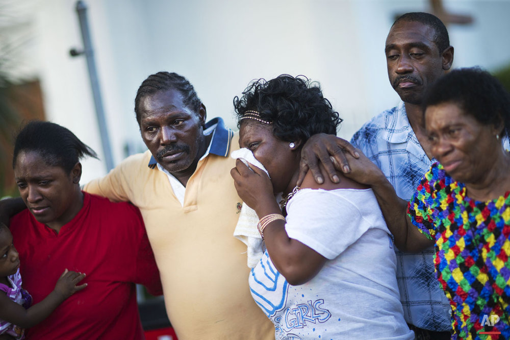 Gary and Aurelia Washington, center left and right, the son and granddaughter of Ethel Lance who died in Wednesday's shooting, leave a sidewalk memorial in front of Emanuel AME Church comforted by fellow family members Thursday, June 18, 2015, in Charleston, S.C. (AP Photo/David Goldman)
