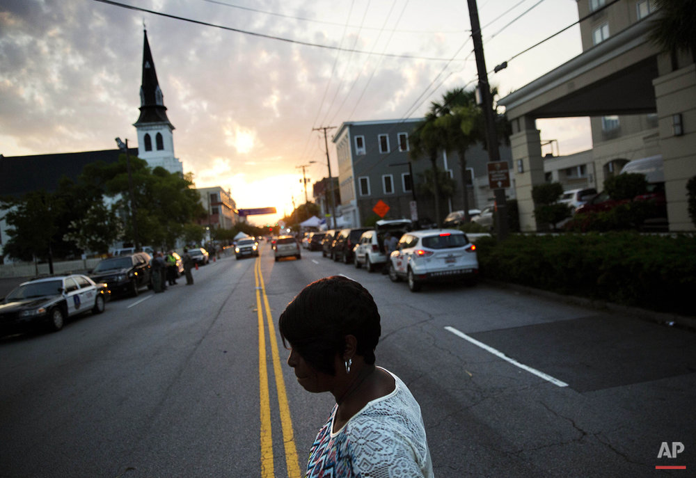A woman crosses the street on her way to visit a sidewalk memorial to the Emanuel AME Church shooting victims as the sun rises next to the church's steeple Sunday, June 21, 2015, in Charleston, S.C. Congregation members say the historic black church where nine people were killed is going to re-open for Sunday morning service. (AP Photo/David Goldman)