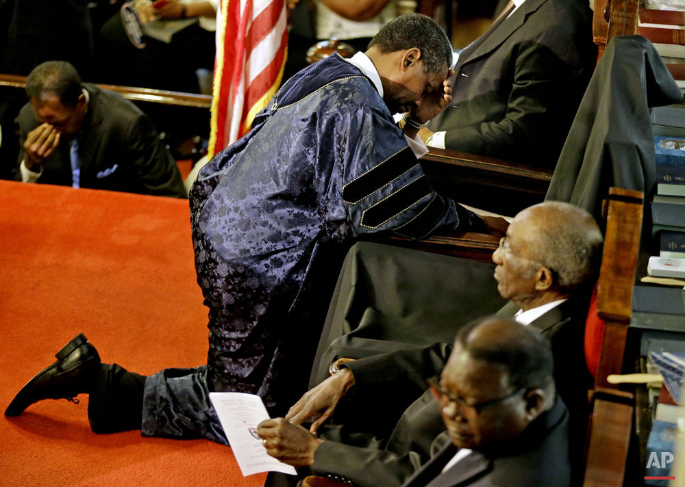 Rev. Norvel Goff prays at the empty seat of the Rev. Clementa Pinckney during the first service at the Emanuel A.M.E. Church Sunday, June 21, 2015, in Charleston, S.C., since a mass shooting claimed the lives of Pinckney and eight others four days earlier. (AP Photo/David Goldman, Pool)