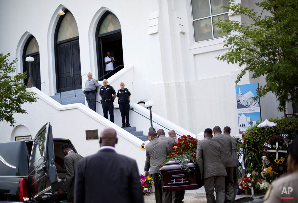Pallbearers carry the casket of Sen. Clementa Pinckney, one of the nine killed in a shooting rampage, from a hearse into Emanuel AME Church for his wake, Thursday, June 25, 2015, in Charleston, S.C. (AP Photo/David Goldman)