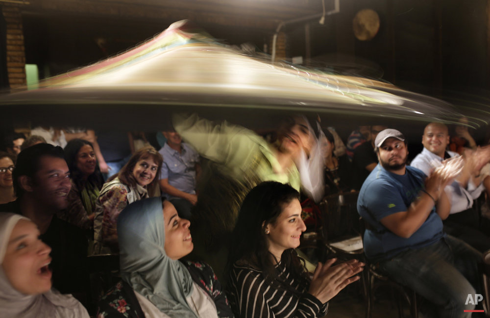 In this Thursday, April 30, 2015 photo, a whirling dervish from the Al-Tannoura Egyptian Heritage Dance Troupe, interacts with the audience, during a performance at the El Dammah Theatre in Cairo, Egypt. Many Egyptians and visitors to Cairo are familiar with the Whirling Dervishes as the stylized spinning dancers who perform across the city at cultural centers, cruise ships, hotels and weddings. (AP Photo/Amr Nabil)