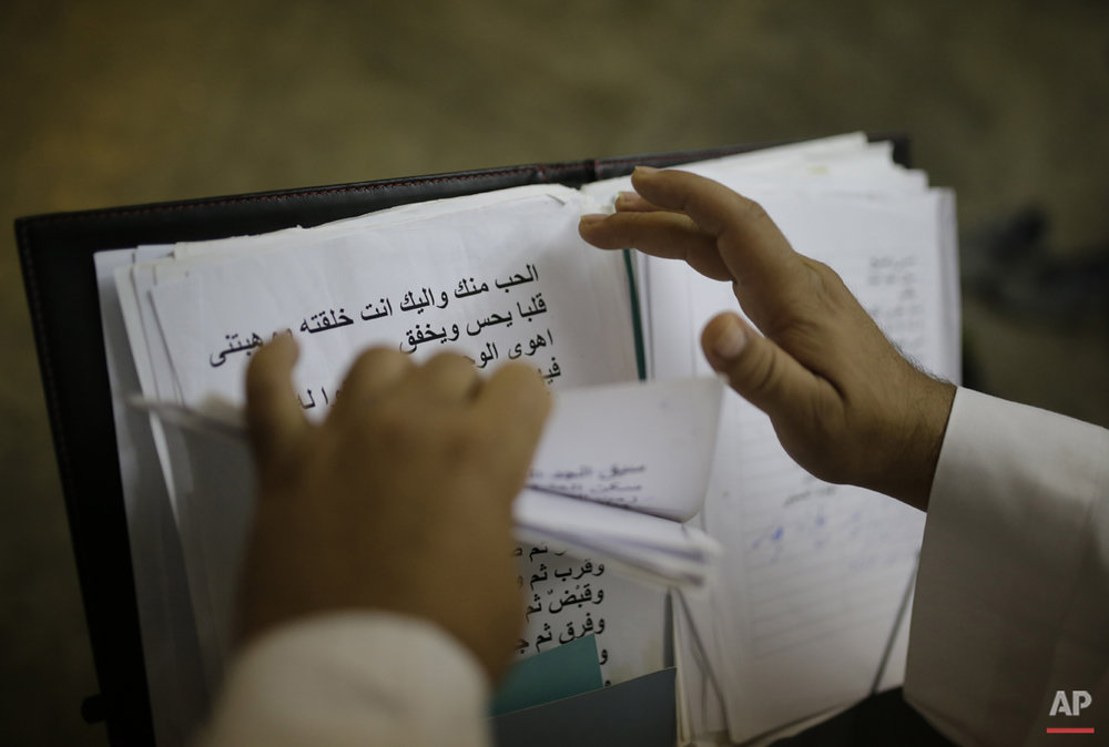"In this Friday, June12, 2015 photo, Amr el-Toney, founder of the Mawlawiyah dervish dance troupe prepares songs ahead of a performance at the Darb 1718 cultural center in Cairo, Egypt. ""We aim to keep the balance between the Sufi recitations and modern signing style, looking to leave our own heritage to the coming generations,"" el-Toney said. ""All of the words of our recitations are about loving God.""  (AP Photo/Amr Nabil)"