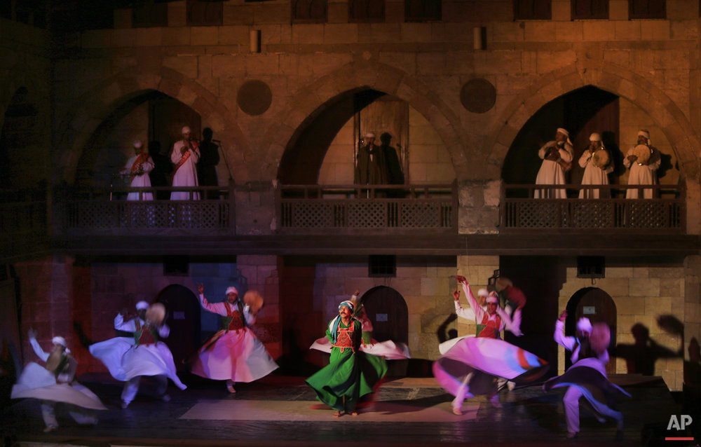 In this Saturday, May 30, 2015 photo, whirling dervishes from the Al-Tannoura Egyptian Heritage Dance Troupe spin during a performance at the 15th century El-Ghouri Palace, in Cairo, Egypt.  (AP Photo/Amr Nabil)