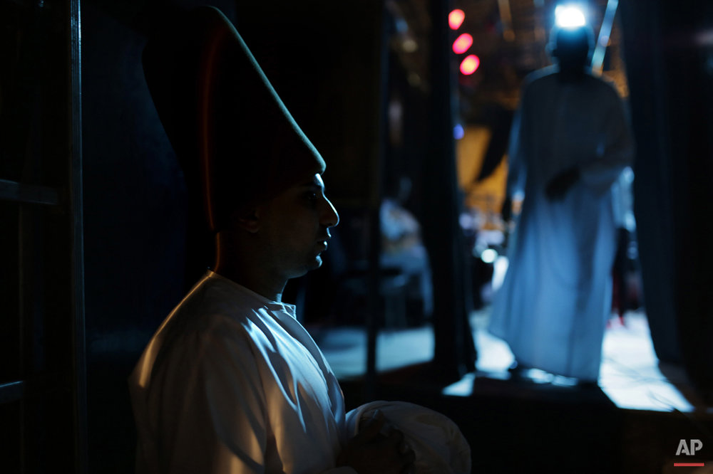 "In this Thursday, May 28, 2015 photo, whirling dervish Ali Taha, a member of the Al-Tannoura Egyptian Heritage Dance Troupe, waits backstage before a performance, at the El Sawy culture center in Cairo, Egypt. ""I'm ready to dance for free, especially with the Mawlawiyah dervishes,"" said Taha. ""While whirling I feel like a white bird flying in the sky."" (AP Photo/Amr Nabil)"