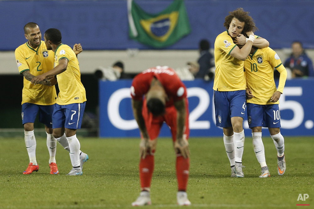 Brazil's Douglas Costa, second left, celebrates his goal against Peru with teammate Brazil's Dani Alves, left, as Brazil's David Luiz, second right, hugs Brazil's Neymar, right, during a Copa America Group C soccer match at the German Becker stadium in Temuco, Chile, Sunday, June 14, 2015. Brazil won the match 2-1. (AP Photo/Silvia Izquierdo)