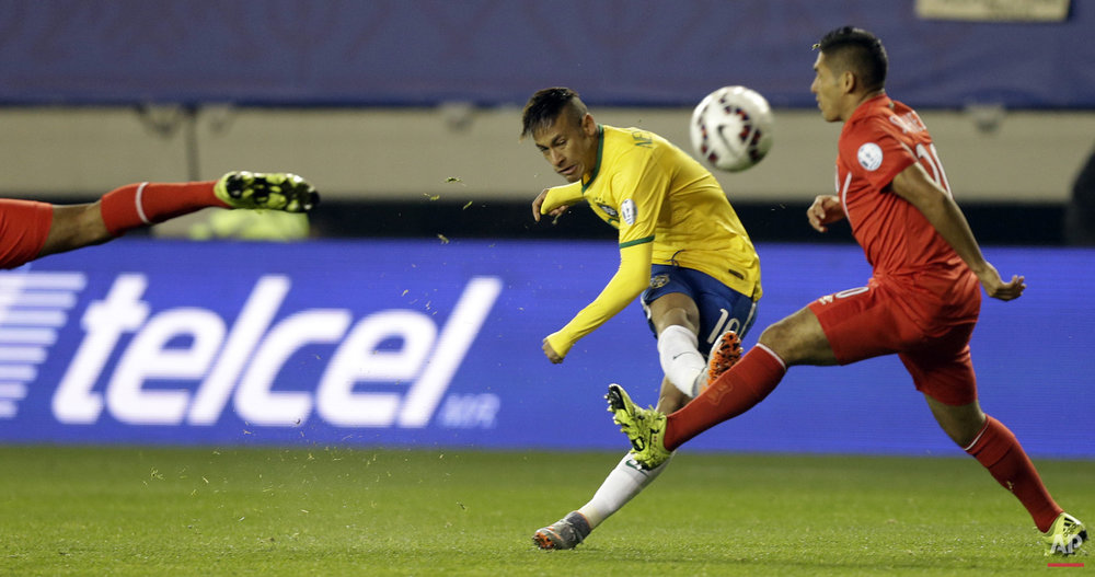 Brazil's Neymar kicks the ball through two Peruvian players during a Copa America Group C soccer match at the Bicentenario Germ·n Becker stadium in Temuco, Chile, Sunday, June 14, 2015. (AP Photo/Jorge Saenz)