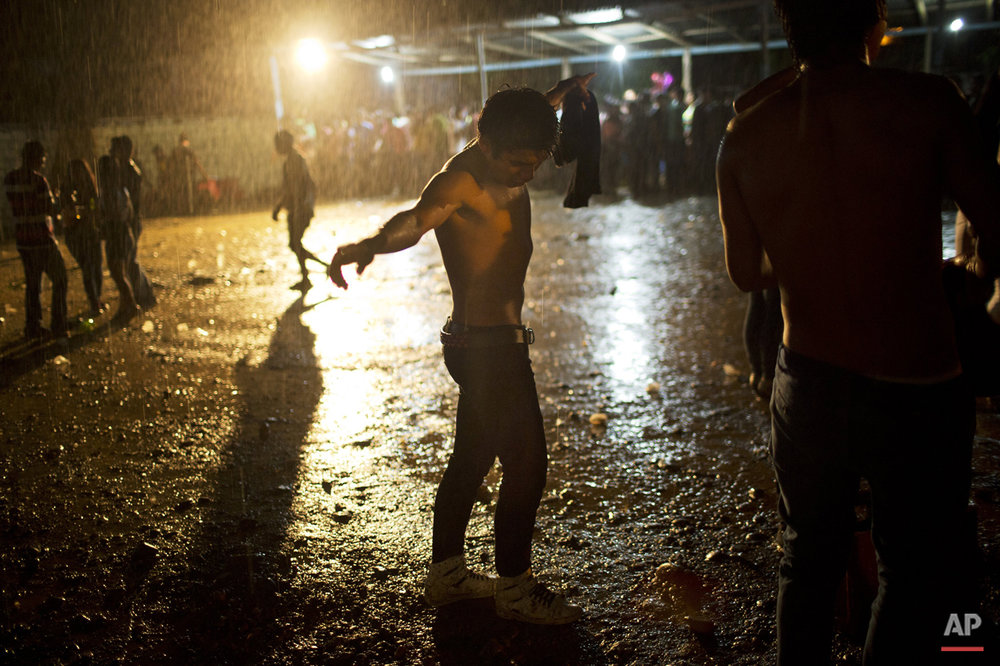 In this March 16, 2015 photo, a young man dances under a heavy rain during Peruvian Huayno singer Ely Corazon's concert, in La Mar, province of Ayacucho, Peru. The average cocaine backpacker or mochilero is surprisingly normal, says sociologist Laura Barrenechea. Few are troublemakers or social misfits. Typically, they are recruited by relatives and friends - often at festivities where liquor flows. They tend not to tell their parents, who nearly always disapprove. (AP Photo/Rodrigo Abd)
