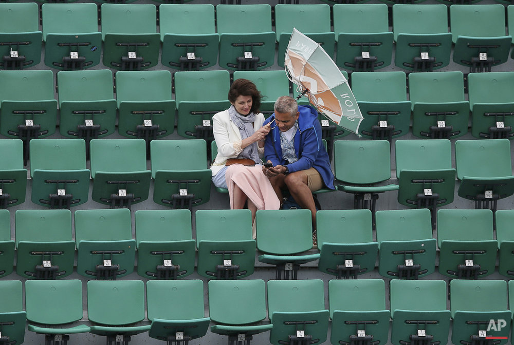 The wind pulls at the umbrella of a spectator as weather conditions suspended the fourth round match between France's Alize Cornet and Ukraine's Elina Svitolina at the French Open tennis tournament at Roland Garros stadium, in Paris, France, Sunday, May 31, 2015. (AP Photo/David Vincent)