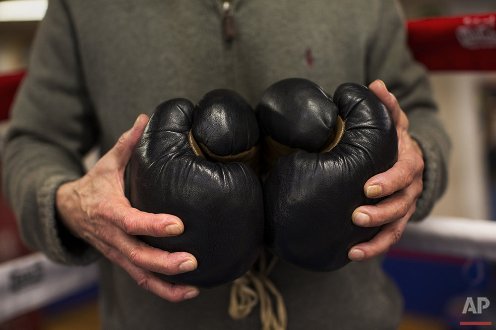 In this Friday, April 29, 2016 photo, boxing coach Manolo del Rio holds a pair of old style boxing gloves at El Rayo boxing gym in Madrid. (AP Photo/Francisco Seco)