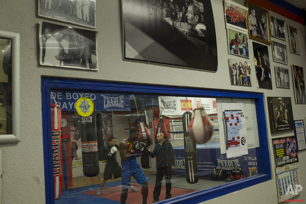 In this Wednesday, April 20, 2016 photo, boxing coach Manolo del Rio, right, talks to his pupils during a training session at El Rayo boxing gym in Madrid. (AP Photo/Francisco Seco)