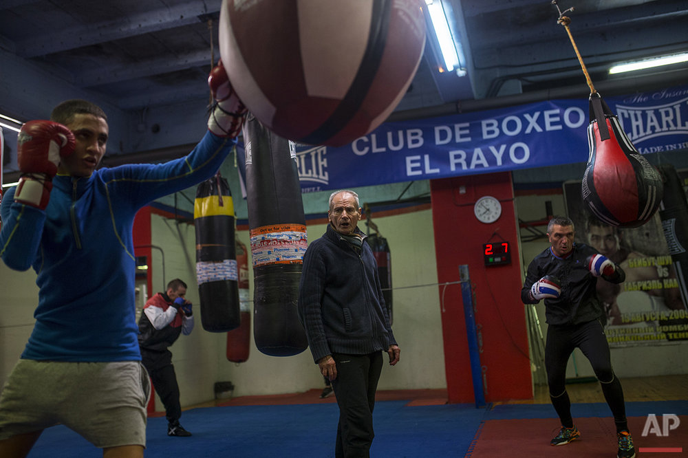 In this Monday, April 25, 2016 photo, boxing coach Manolo del Rio, centre, 84, talks to his pupil Mohammed Naamane, 19, left, during a training session at El Rayo boxing gym in Madrid. (AP Photo/Francisco Seco)