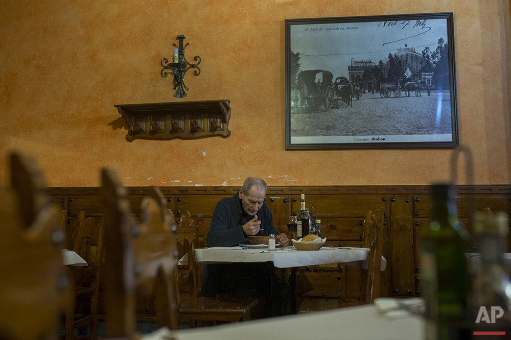 In this Wednesday, May 18, 2016 photo, boxing coach Manolo del Rio, 84, has a meal during a lunch break in a restaurant near his daily working El Rayo boxing gym in Madrid. (AP Photo/Francisco Seco)