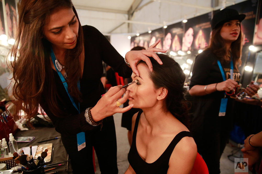 In this Feb. 1, 2017 photo, a makeup artist applies eye-shadow on Anjali Lama, a transgender model from Nepal, during Lakme Fashion week in Mumbai, India. Growing up as the fifth son in a poor farming family in rural Nepal the dream to be a fashion model came late in life. First came a long, painful struggle to accept that he felt deeply female. It was a chance encounter with a group of transgender women that turned Lama's life around by putting her in touch with the Blue Diamond Society, an advocacy group for Nepal's LGBT community. In 2005, she came out to her friends and family as a transgender woman. (AP Photo/Rafiq Maqbool)