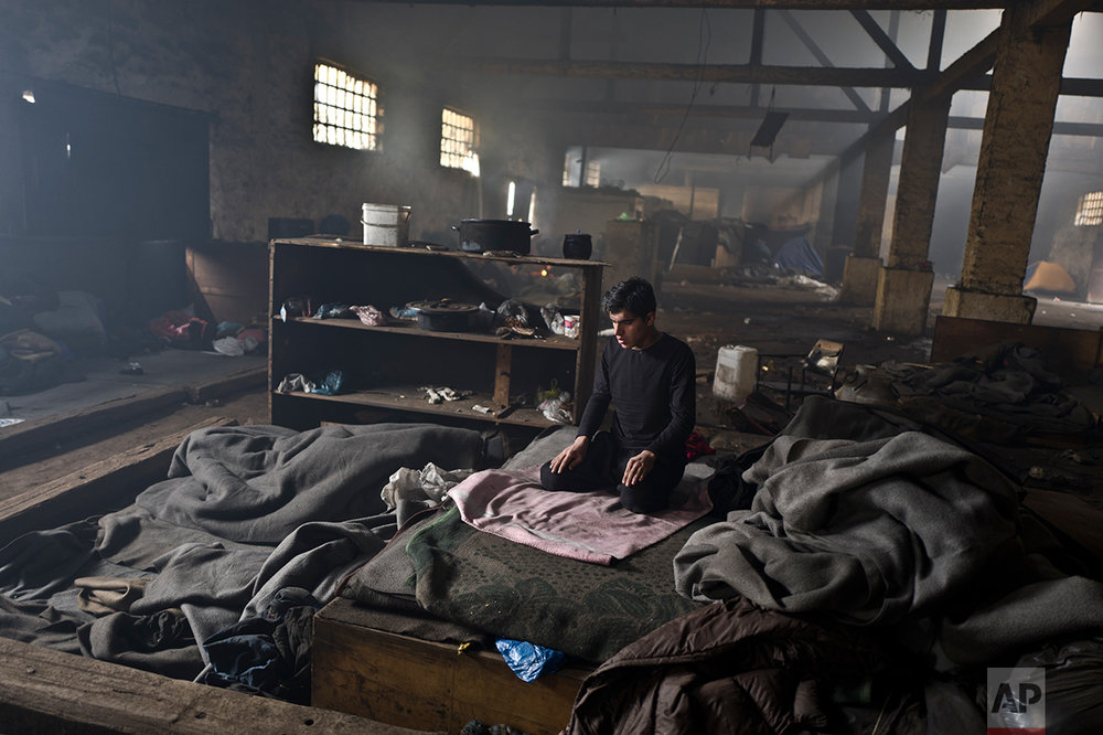 An Afghan refugee prays in an abandoned warehouse where he and other migrants took refuge in Belgrade, Serbia, Friday, Feb. 3, 2017.  (AP Photo/Muhammed Muheisen)
