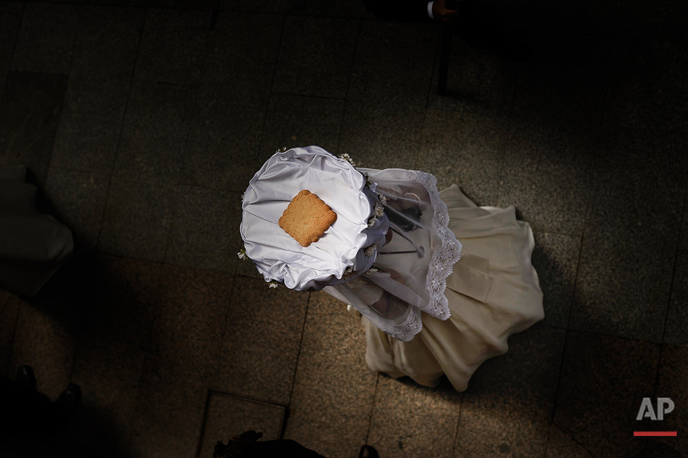 A participant of the ''Bread Procession of the Saint'', takes part in the ceremony in honor of Domingo de La Calzada Saint (1019-1109) in Santo Domingo de La Calzada, northern Spain, Wednesday, May 11, 2016. Every year during spring season, ''Las Doncellas'' (White Virgins), hold on their head a basket covered with white cloth while they walk through this old village in honor of the saint.  (AP Photo/Alvaro Barrientos)
