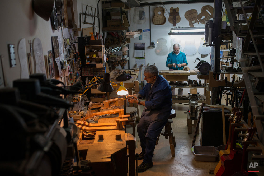 In this Tuesday, Nov. 10, 2015 photo, two Spanish guitar makers work at a workshop in Madrid. Spanish flamenco guitars are known for their beautiful shape, rich wood colors and full-bodied, crisp musical tones. (AP Photo/Francisco Seco)