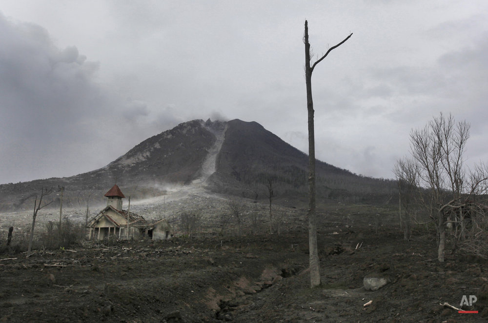 In this Monday, Nov. 16, 2015 photo, a church is seen dwarfed by Mount Sinabung at the abandoned village of Simacem, North Sumatra, Indonesia. The village is located within an area which, following the eruption of the volcano, has been declared too dangerous to inhabit, forcing its residents to abandon their homes. (AP Photo/Binsar Bakkara)