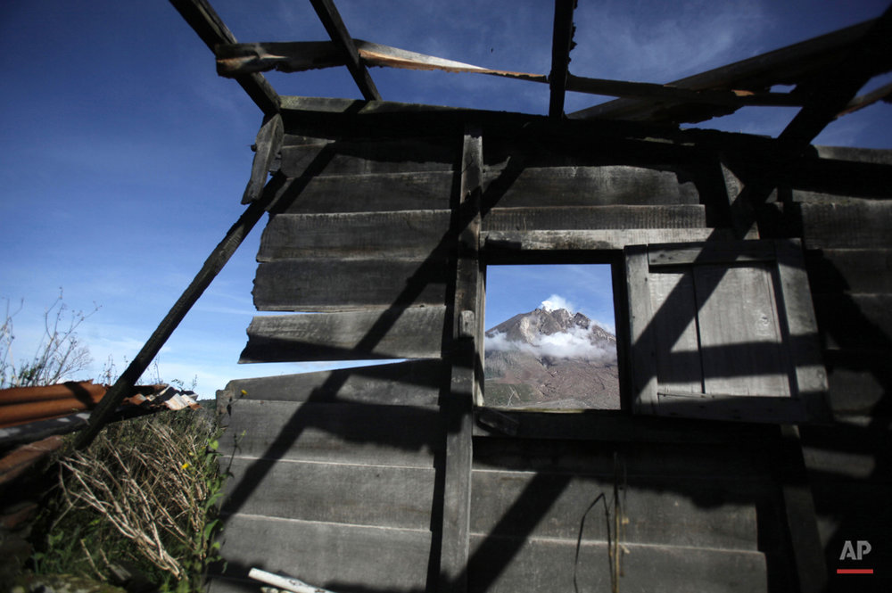 In this Thursday, Nov. 12, 2015 photo, the peak of Mount Sinabung is seen through a window of a burnt out house at the abandoned village of Sibintun, North Sumatra, Indonesia. The village is located within an area which, following the eruption of the volcano, has been declared too dangerous to inhabit, forcing its residents to abandon their homes. (AP Photo/Binsar Bakkara)