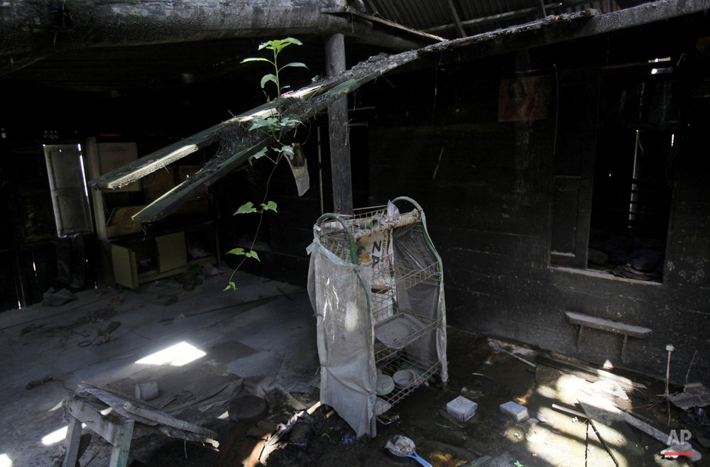 This Thursday, Nov. 12, 2015 photo shows the interior of a house abandoned following the eruption of Mount Sinabung in the village of Guru Kinayan, North Sumatra, Indonesia. The village is located within an area which, following the eruption of the volcano, has been declared too dangerous to inhabit, forcing its residents to abandon their homes. (AP Photo/Binsar Bakkara)