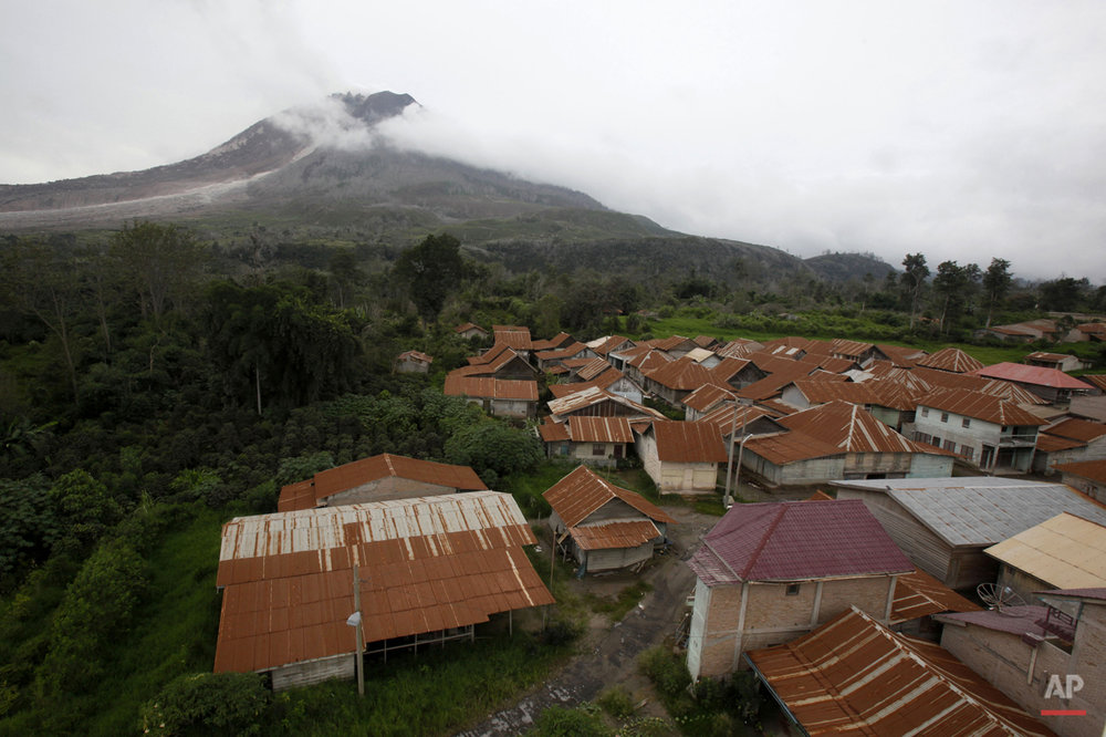 In this Monday, Nov. 16, 2015 photo, Mount Sinabung looms above the village of Sukanalu which was abandoned following its eruption, in North Sumatra, Indonesia. The village is one of few others located within an area which, following the eruption of the volcano, has been declared too dangerous to inhabit, forcing its residents to abandon their homes. (AP Photo/Binsar Bakkara)